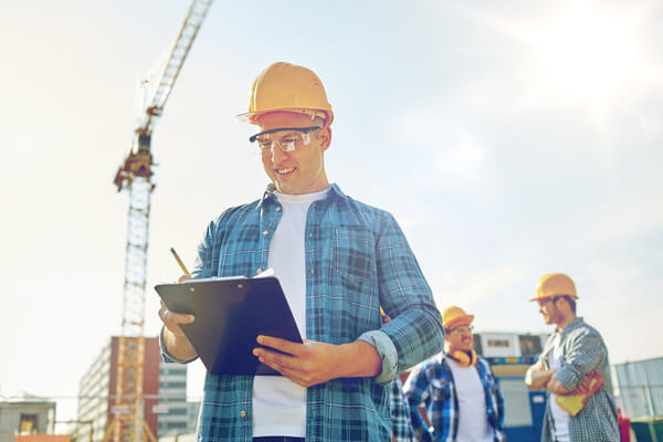 Construction worker looking at clipboard at construction site