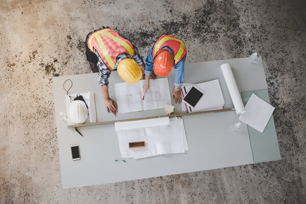 two construction workers looking over construction plans