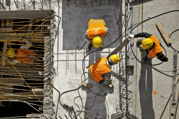 Three construction workers at construction site