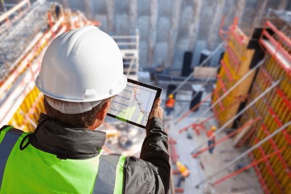 Construction worker overlooking construction site wile looking at a tablet