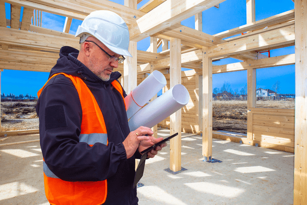 construction worker looking at phone while at construction site