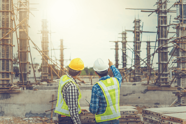 two construction workers pointing at construction site